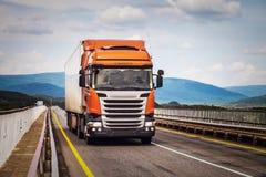 Orange lastbil på en väg arkivfoton