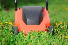 Orange Lawn mower cutting grass. Gardening concept background Royalty Free Stock Photo