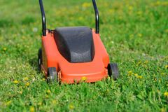 Orange Lawn mower cutting grass. Gardening concept background Stock Images