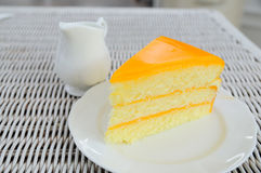 Orange layer cake on white plate put on rattan table. Stock Images