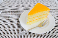 Orange layer cake on white plate put on rattan table. Royalty Free Stock Images