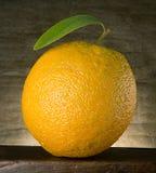 Orange with leaf. Orange with green leaf on wood Stock Photos