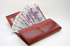 Orange leather wallet full of one hundred roubles Stock Images