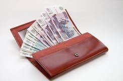 Orange leather wallet full of one hundred roubles. Orange leather wallet full of one hundred rouble on light background Stock Images