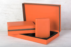 Orange leather wallet and gift box set on grunge white wood back. Orange leather wallet and gift box set on grunge wood background Stock Images
