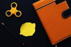 Orange lekmanna- foto för anteckningsbok- och spinnarelägenhet på svart bakgrund Royaltyfri Fotografi