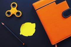 Orange lekmanna- foto för anteckningsbok- och spinnarelägenhet på svart bakgrund Royaltyfria Foton