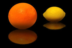 Orange and lemon on a black background Stock Photos