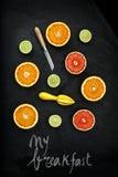Orange and lemon cut on black stone Stock Photos