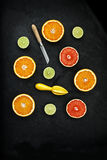 Orange and lemon cut on black stone Royalty Free Stock Images