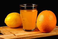 Orange, lemon and glass of juice on a black background Stock Image