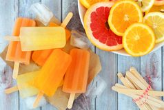 Orange, lemon and grapefruit ice pops, overhead scene on wood. Orange, lemon and grapefruit ice pops, overhead scene on a rustic wood background Royalty Free Stock Photography