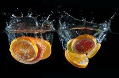 Orange, lemon, grapefruit and lime splashing into water Royalty Free Stock Photo