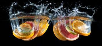 Orange, lemon, grapefruit and lime splashing into water Stock Photo