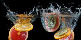 Orange, lemon, grapefruit and lime splashing into water Royalty Free Stock Images