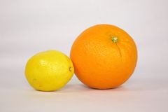 Orange and Lemon. A lemon and orange sit side-by-side against a white background stock image