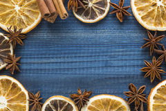 Orange and lemon slices with star anise and cinnamon on blue wooden background Royalty Free Stock Photography
