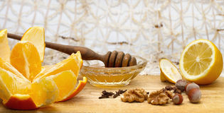 Orange, lemon and small bowl with honey and honey dipper on wooden table with hazelnuts, walnuts and cloves Royalty Free Stock Photos