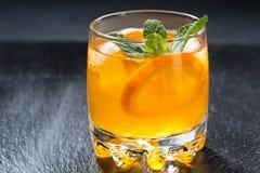Orange lemonade with ice in a glass, closeup Stock Image