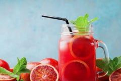 Orange lemonade or juice decorated mint leaves in glass jar on turquoise background. Orange lemonade or juice decorated mint leaves in glass jar on blue Royalty Free Stock Image
