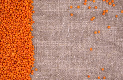 Orange lentils on a linen background Royalty Free Stock Photos