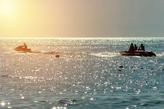 Orange Licht des blauen Himmels auf dem Sonnenuntergang Schattenbild eines Bananenboots-Jet-Skis haben Spa? lizenzfreie stockfotos