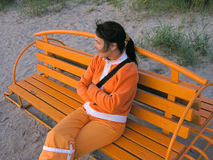 Orange life. Girl sitting on an orange beach bench in orange clothing, looking away. Downward shot. Dim lighting conditions Stock Image