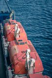 Orange life boats attached to cruise ship deck royalty free stock image