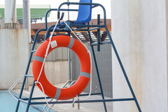 Orange Life Buoy attached to life guard stand Stock Photos