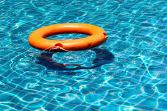 Orange life buoy floating on the surface of blue water Royalty Free Stock Photo