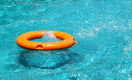Orange life buoy floating on the surface of blue water Royalty Free Stock Photos