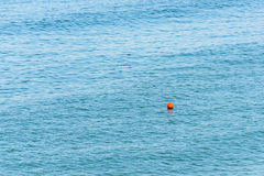 Orange Life Buoy In The Middle Of The Ocean Royalty Free Stock Image