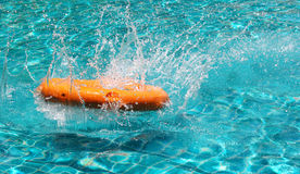 Orange life buoy is splashing with clear blue water in swimming Royalty Free Stock Image