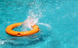 Orange life buoy is splashing with clear blue water in swimming Stock Image