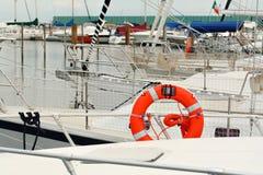 Orange life buoy on white yacht berthed at marina Royalty Free Stock Images