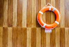 The orange life buoy with the wood wall background, for safety a Royalty Free Stock Photography
