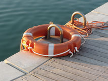 Orange life buoy on wooden pier in the harbor in Marina di Pisa, Tuscany, Italy Stock Image