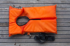 Orange life jacket. Old rescue vintage lifevest object for safe sailing isolated on wooden background Stock Photo