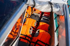 Orange life jacket on the boat. Safety stock photos