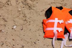Orange life jacket lying on the sand. Safety on the water. Orange life jacket lying on the sand. The concept of Safety on the water royalty free stock photo
