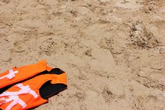 Orange life jacket lying on the sand. Safety on the water. Orange life jacket lying on the sand. The concept of Safety on the water stock images