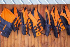 Orange life jackets hanging on a wooden wall. Life vest for rent royalty free stock photography