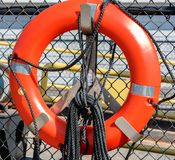 Orange Life Preserver hanging on a commercial ferry dock. An orange life preserver hanging on a working ferry dock Stock Photography