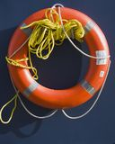 Orange Life Preserver Ring. With a rope on a blue background in the sun royalty free stock photos