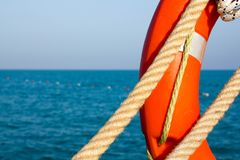 Orange life preserver and two Maritime rope on the background of blue sea and sky. Close up. Lifebuoy on the background of the sea royalty free stock photography