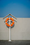 Orange life ring on the pier. Orange life buoy on the pier. Vintage film look Royalty Free Stock Image