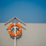 Orange life ring on the pier. Orange life buoy on the pier. Vintage film look Stock Image