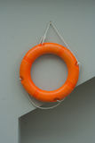 Orange life ring with white rope hanging on gray wall. Royalty Free Stock Photo