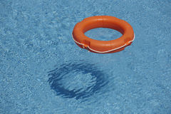 Orange life rings in blue water royalty free stock images