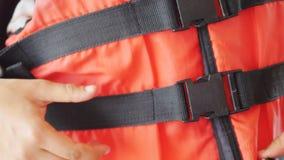 Orange life safety jacket and hand wearing it Stock Image